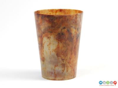 Side view of a beaker showing the marbled material.